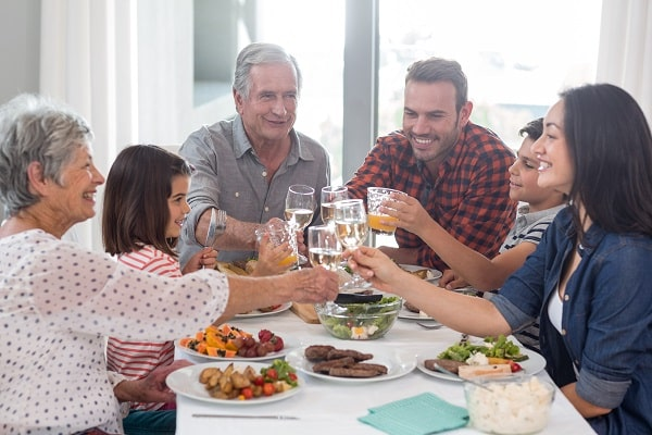 Family Enjoying Meal And Toasting Glasses