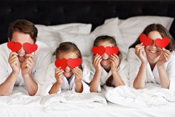 Family Laying In A Bed With Heart Cutouts