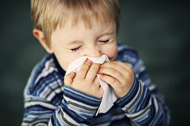 Young Boy Sneezing Into Tissue